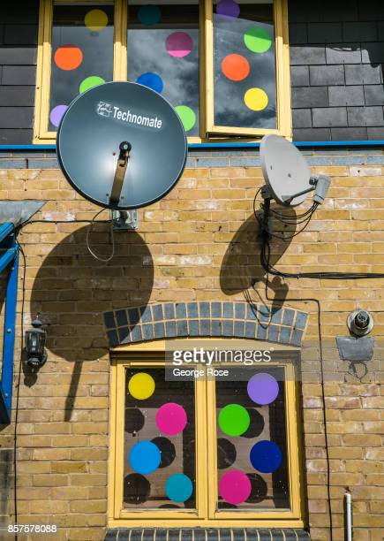 Satellite dishes are mounted outside a colorfully decorated apartment near Maiden Lane on September 13 in London England Great Britain's move toward...
