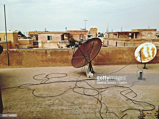 Satellite Dishes On Roof Of House Against Sky In City