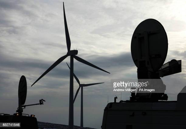 Satellite dishes on television trucks are seen sillhouetted next to a wind turbine as Trade and Industry Secretary Alistair Darling officially opens...