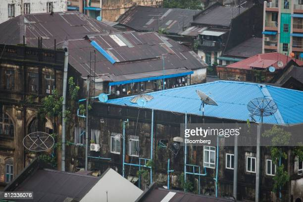 Satellite dishes stand on the roofs of residential buildings in Yangon Myanmar on Wednesday June 14 2017 In 2015 Myanmar signed up more people for...