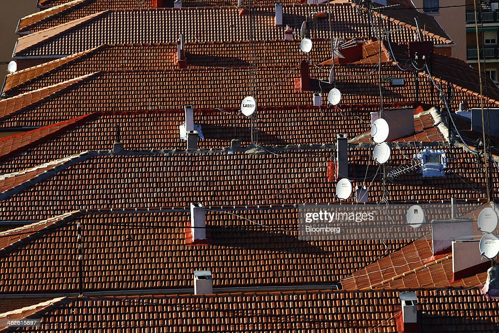 Satellite dishes stand on the tiled rooftops of residential housing in Madrid, Spain, on Monday, Jan. 13, 2014. Spain's rental market is growing as government-spending cuts, a 26 percent jobless rate and subdued mortgage lending make home buying more difficult. Photographer: Angel Navarrete/Bloomberg via Getty Images