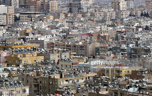 Satellite dishes water tanks and solar panels on rooftops in the city of Sanliurfa south eastern Turkey