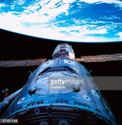 A satellite orbiting above earth : Stock Photo