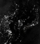 Satellite view of the Korean Peninsula showing city lights at night.
