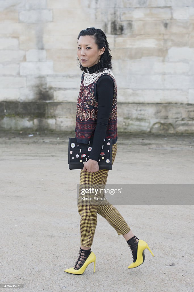 Satine Boutique Owner Jeannie Lee wears a Dries Van Noten top, Shibuya trousers, Saint Laurent shoes, Wolford socks and Lizzie Fortunato bag on day 3 of Paris Collections: Women on February 27, 2014 in Paris, France.