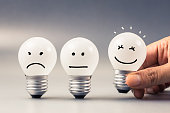 Hand choose a smile light bulb from satisfaction evaluation