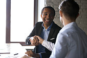 Happy satisfied black client shaking hands thanking manager for good financial deal, african american businessman handshaking partner after successful business negotiations, hiring, buying services