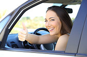 Portrait of a satisfied driver gesturing thumbs up sitting inside a car