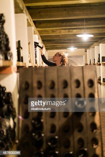 Satisfied Female Vintner Checking Wine Bottles, Cellar in Europe