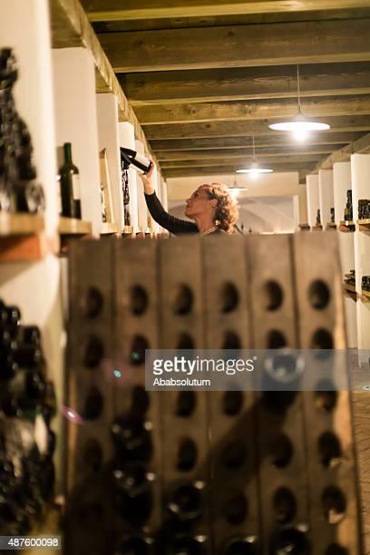 満足する女性のチェックのワインボトルワイン醸造業者、ヨーロッパのワインセラー