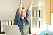 Portrait of a young satisfied intern raising arms at office