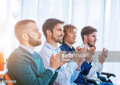 Satisfied people applaud after presentation