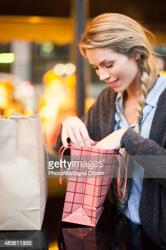 Satisfied shopper examining her purchases : Stock Photo