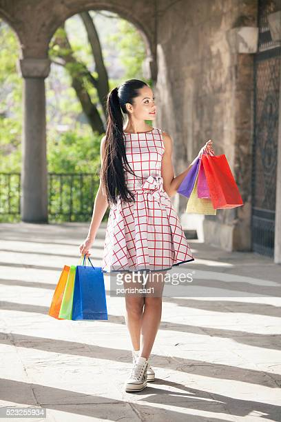 Satisfied young woman holding colored purcheses