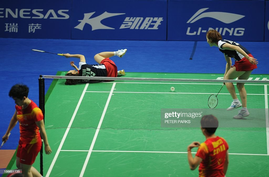 Satoki Suetsuna of Japan (top L) takes a fall as her teammate Miyuki Maeda (top R) looks on in their game against Wang Xiaoli (bottom R) and Yu Yang (bottom L) in the women's doubles final at the China Open badminton tournament in Shanghai on November 18, 2012. AFP PHOTO/Peter PARKS