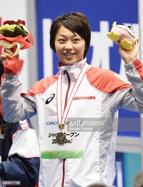 Satomi Suzuki of Japan celebrates on the podium after winning the women 50m Breaststroke and breaking Japan record during day two of the Japan Open...