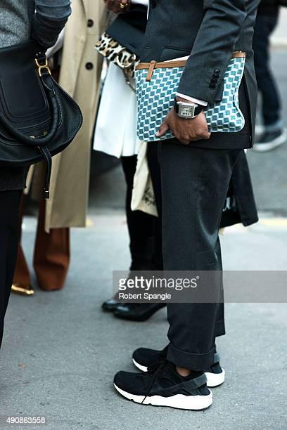 Satoshi Matsubara wears grey flannel suit with Goyard clutch Cartier watch and black Nike Huarache sneakers after Cloe on Avenue du General...