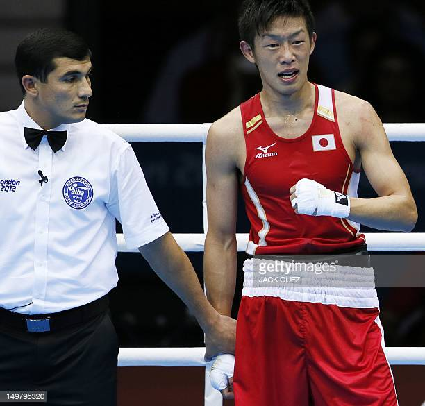 Satoshi Shimizu of Japan stands with Turkmen boxing referee Ishanguly Meretnyyazov awaiting the judges' call following his match against Magomed...