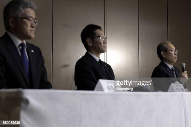 Satoshi Tsunakawa president of Toshiba Corp right speaks as Masayoshi Hirata chief financial officer of Toshiba Corp center and Mamoru Hatazawa vice...