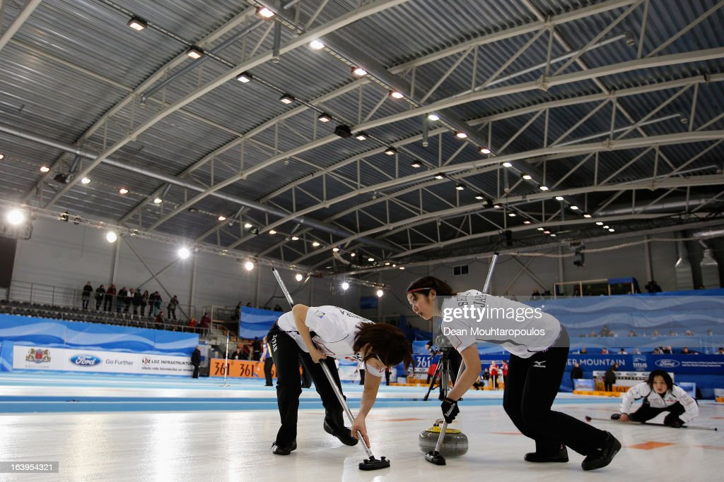 Satsuki Fujisawa looks on after she throws the stone as Emi Shimizu (R) and Chiaki Matsumura (L) all of Japan sweep in the match between Japan and Scotland during Day 3 of the Titlis Glacier Mountain World Women's Curling Championship at the Volvo Sports Centre on March 18, 2013 in Riga, Latvia.