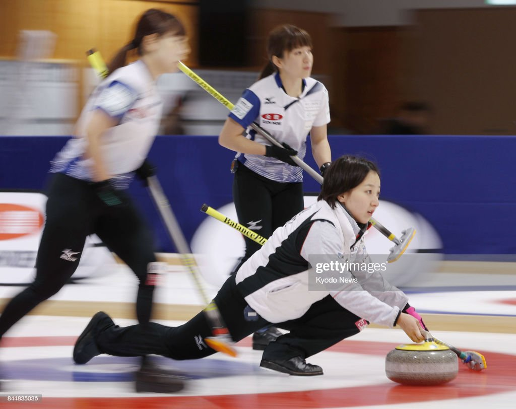Satsuki Fujisawa (bottom) of LS Kitami throws a shot during a game against Chubu Electric Power in a qualifying playoff for the Pyeongchang Winter Olympics, in Kitami, Hokkaido, on Sept. 9, 2017. Kitami moved within one win of securing a spot at the Olympics in February after taking a 2-1 lead over Chubu. ==Kyodo