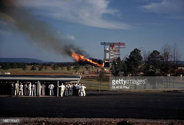 Saturn Space Project Aux EtatsUnis en 1963 allumage de la fusée Saturne I sur son socle de départ au premier plan des hommes en combinaison regroupés...