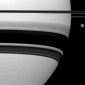 Saturn's largest moon Titan looks small here pictured to the right of the gas giant in this Cassini spacecraft view