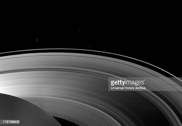 Saturn's moon Tethys casts a shadow on the planet's A ring alongside the larger shadow cast by the planet itself Cassini