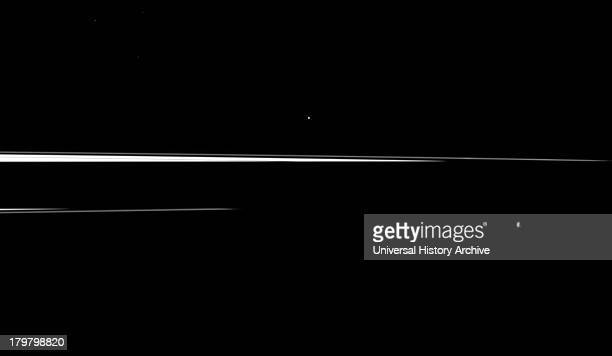Saturn's shadow interrupts the planet's rings leaving just thin slivers of the rings visible in this image which shows a pair of the planet's small...