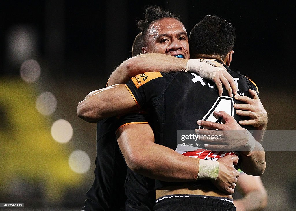 Sauaso Sue of the Tigers is congratulated by team mates after scoring a try during the round 22 NRL match between the Canberra Raiders and the Wests Tigers at GIO Stadium on August 10, 2015 in Canberra, Australia.