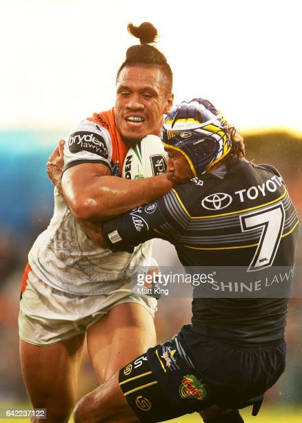 Sauaso Sue of the Tigers is tackled by Johnathan Thurston of the Cowboys during the NRL Trial match between the Wests Tigers and the North Queensland...