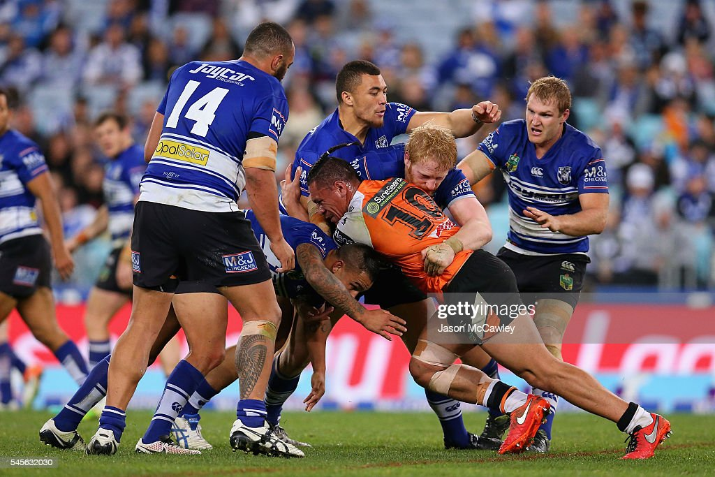 Sauaso Sue of the Tigers is tackled during the round 18 NRL match between the Canterbury Bulldogs and the Wests Tigers at ANZ Stadium on July 9, 2016 in Sydney, Australia.