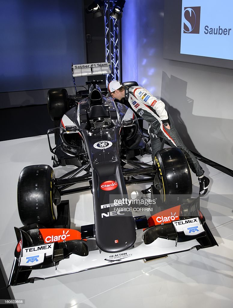 Sauber F1 team driver, Nico Hulkenberg, from Germany looks inside the new Sauber C32-Ferrari car for 2013 Formula One season during the unveil event on February 2, 2013 in Hinwil, Switzerland. AFP PHOTO / FABRICE COFFRINI
