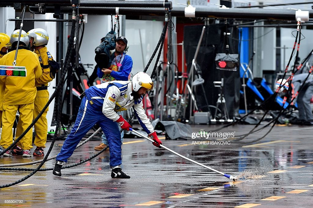 Sauber F1 Team's mechanic wipes the water after a heavy rainfall in the pit lane at the Monaco street circuit, on May 29, 2016 in Monaco, during the Monaco Formula 1 Grand Prix. / AFP / POOL / ANDREJ