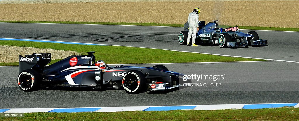Sauber's German driver Nico Hulkenberg (L) passes by Mercedes' German driver Nico Rosberg checking his new car after it burned during a training session at the Jerez de la Frontera racetrack on February 5, 2013.