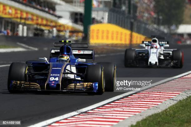 Sauber's German driver Pascal Wehrlein and Williams' British reserve driver Paul di Resta race at the Hungaroring circuit in Budapest on July 30...