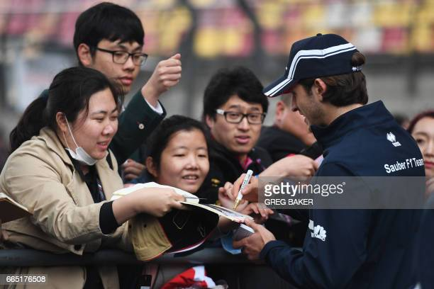 Sauber's Italian driver Antonio Giovinazzi signs autographs for fans in Shanghai on April 6 ahead of the Formula One Chinese Grand Prix / AFP PHOTO /...