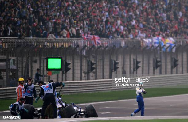 Sauber's Italian driver Antonio Giovinazzi walks away after crashing his car during the qualifying session of the Formula One Chinese Grand Prix in...