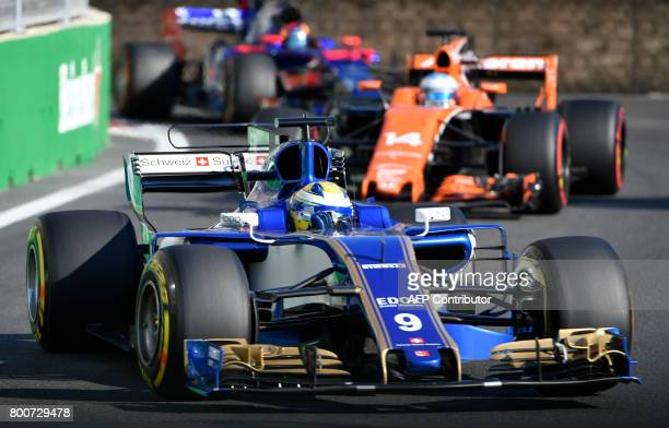 Sauber's Swedish driver Marcus Ericsson and McLaren's Spanish driver Fernando Alonso steer their cars during the Formula One Azerbaijan Grand Prix at...