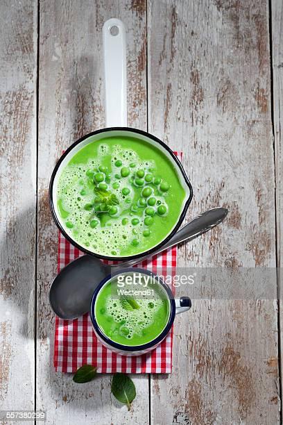 Saucepan and mug of pea soup, spoon and cloth on wood