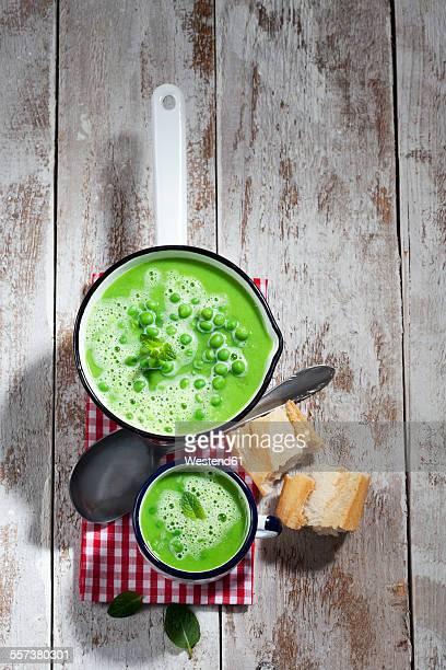 Saucepan and mug of pea soup, spoon, sliced baguette and cloth on wood