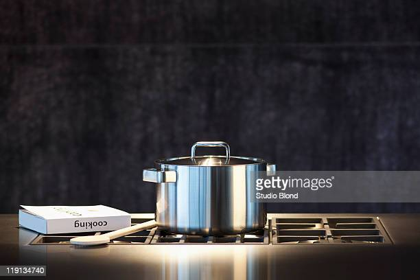 Saucepan, cookery book and wooden spoon on hob.