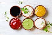 Sauces ketchup, mustar, mayonnaise, wasabi, soy sauce in clay bowls on wooden white background