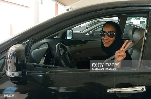 Saudi activist Manal Al Sharif who now lives in Dubai flashes the sign for victory as she drives her car in the Gulf Emirate city on October 22 in...