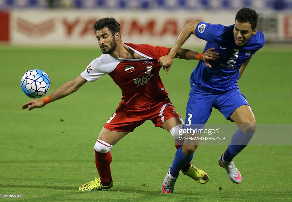 Saudi Al-Hilal Brazilian player Carlos Eduardo (R) fights for the ball against Shoja Khalizadeh (L) of Iranian club Tractorsazi during their Asian Champions League group C football match at the Sultan Qabous stadium in Muscat on May 3, 2016. / AFP / MOHAMMED