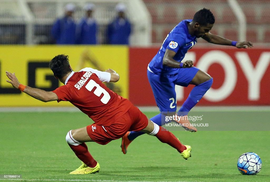 Saudi Al-Hilal club player Nawaf al-Abid fights for the ball against Shoja Khalilzadeh of Iranian club Tractorsazi during their Asian Champions League group C football match at the Sultan Qabous stadium in Muscat on May 3, 2016. Al-Hilal won the match 2-1. MAHJOUB