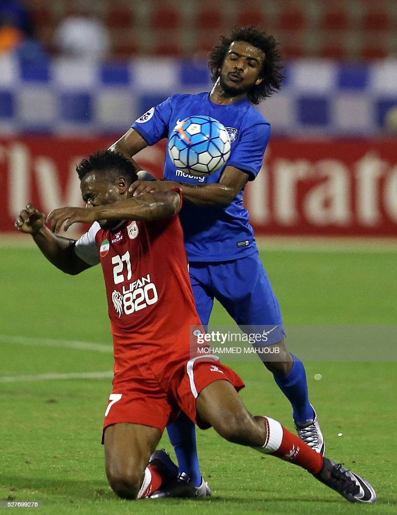 Saudi Al-Hilal club player Yasir al-Shahrani fights for the ball against Aloys Nong of Iranian club Tractorsazi during their Asian Champions League group C football match at the Sultan Qabous stadium in Muscat on May 3, 2016. Al-Hilal won the match 2-1. / AFP / MOHAMMED