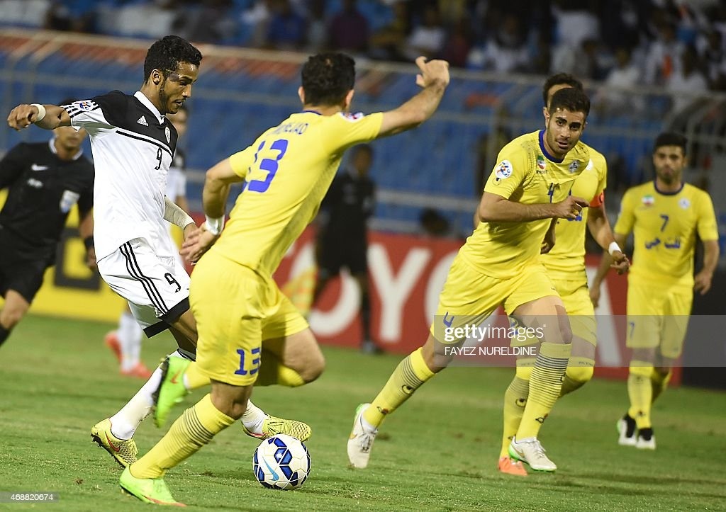 Saudi al-Shabab's Nayef Hazazi (L) dribbles past Iranian Naft Tehran's Vahid Hamdinejad (C) during the AFC Champions League Group B football match on April 7, 2015 at Prince Faisal Bin Fahd Stadium in Riyadh.