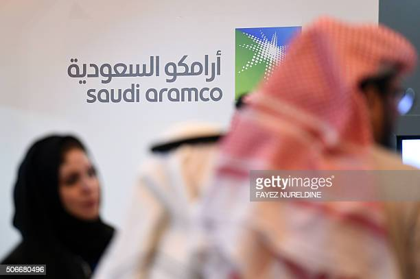 Saudi and Foreign investors stand in front of the logo of Saudi state oil giant Aramco during the 10th Global Competitiveness Forum on January 25 in...