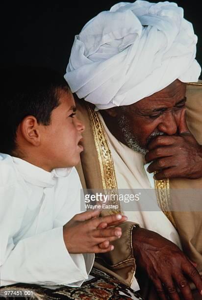 Saudi Arabia, boy with adult in traditional Bedouin costume